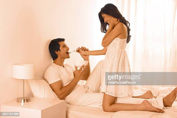 Full length of young woman feeding man in bed