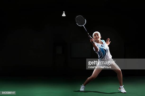 Full length of young woman hitting shuttlecock with badminton racket at court