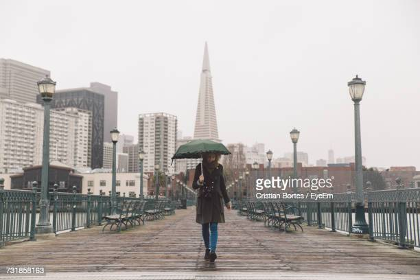 Full Length Of Young Woman Holding Umbrella Walking On Pier Against Transamerica Pyramid