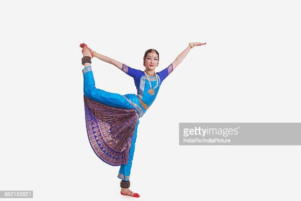 Full length of young woman performing Bharat Natyam dance over white background