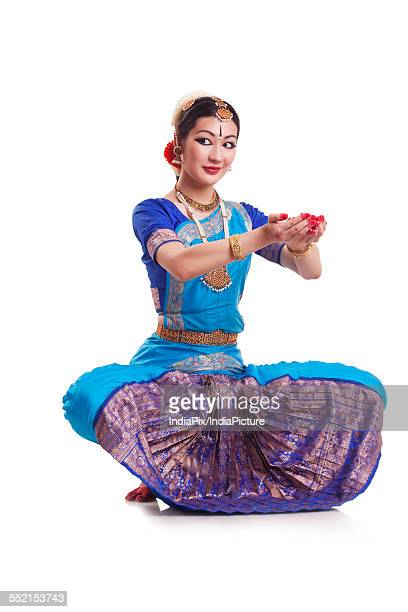 Full length of young woman performing Bharatanatyam over white background