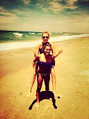 Full length of young woman piggybacking friend on beach