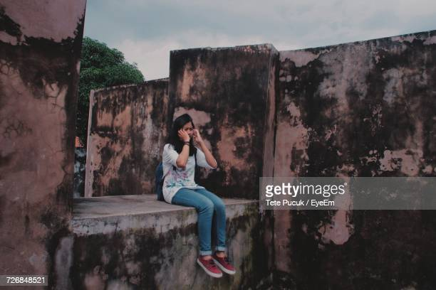 Full Length Of Young Woman Sitting On Retaining Wall
