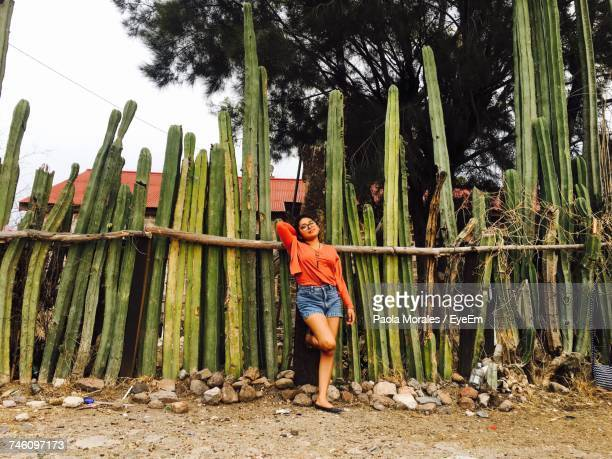 Full Length Of Young Woman Standing Against Cactus Plants