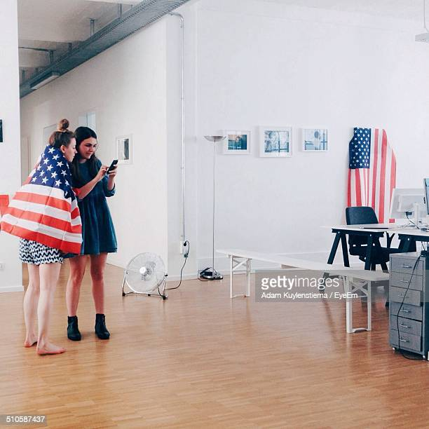 Full length of young women with American flag using mobile phone in office