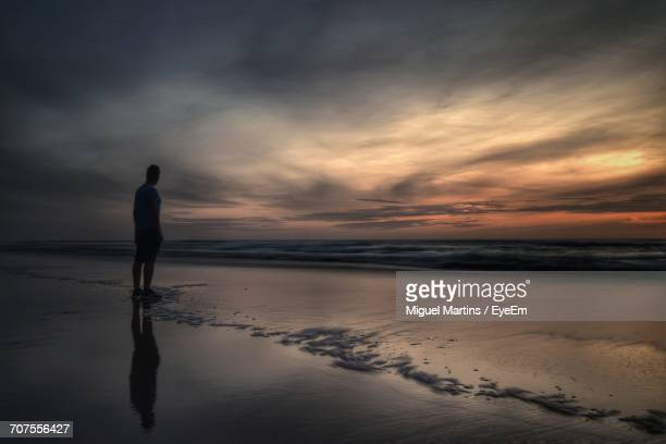 Full Length On Man Standing On Shore At Beach Against Cloudy Sky