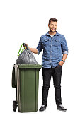 Full length portrait of a guy taking out the garbage isolated on white background