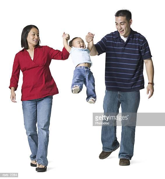full length portrait of a young adult couple as the hold hands with a swing their young daughter
