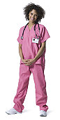 full length portrait of a young adult female nurse in pink scrubs as she smiles