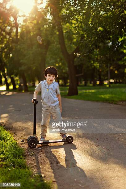 Full length portrait of back lit boy with scooter
