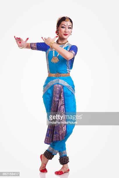 Full length portrait of beautiful woman performing Bharatanatyam on white background