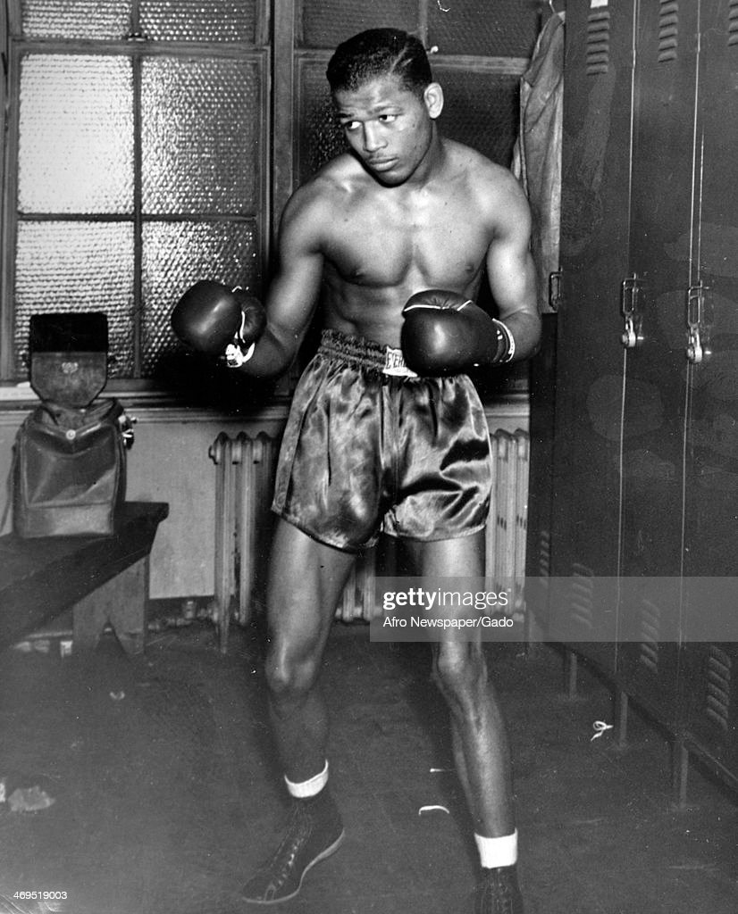A full length portrait of boxing champion Sugar Ray Robinson in fighting pose standing in a locker room wearing boxing gloves shorts and shoes June 1...