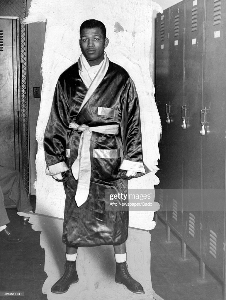 A full length portrait of boxing champion Sugar Ray Robinson standing in a locker room wearing a boxing robe gloves and shoes September 14 1946