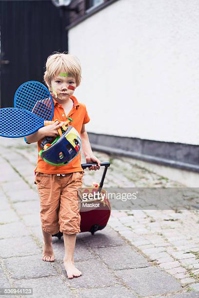Full length portrait of boy pulling luggage while holding tennis rackets and helmet on street