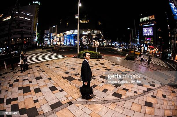 Full Length Portrait Of Businessman Standing On Sidewalk In City At Night
