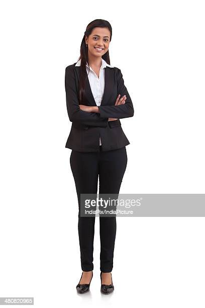 Full length portrait of confident businesswoman standing arms crossed over white background