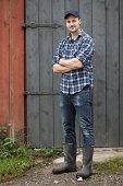 Full length portrait of confident farmer standing arms crossed against barn