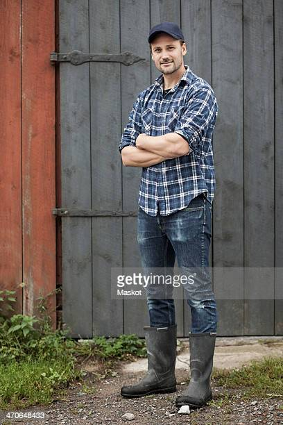 Full length portrait of confident farmer standing arms crossed against barn