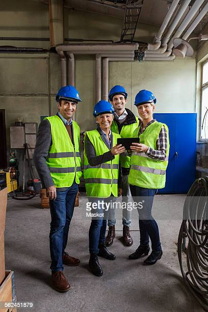Full length portrait of confident manual workers using digital tablet in factory