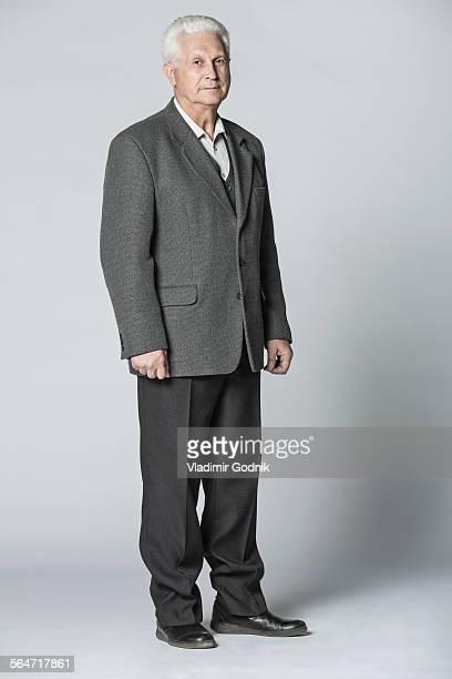Full length portrait of confident senior man standing over gray background