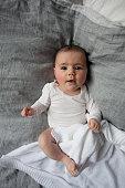 Full length portrait of cute baby girl lying in bed