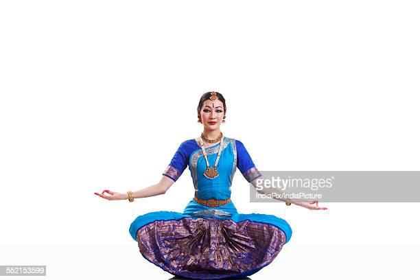 Full length portrait of dancer performing Bharatanatyam against white background