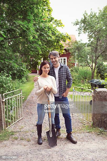 Full length portrait of farming couple standing at entrance of organic farm