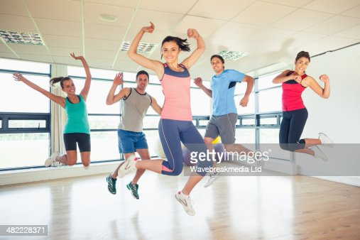 Fitness class and instructor jumping in fitness studio : Foto de stock