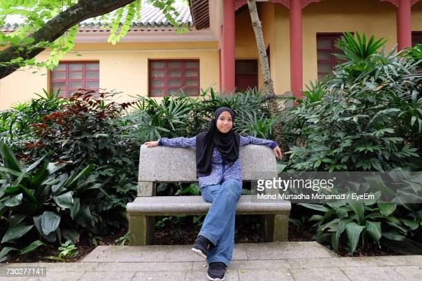 Full Length Portrait Of Girl Wearing Hijab Sitting On Bench