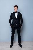 Full length portrait of handsome groom holding hands in pockets