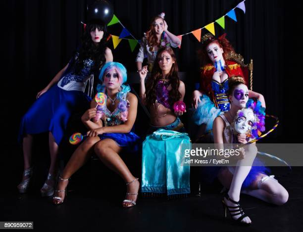 Full Length Portrait Of Happy Friends In Costume Sitting Against Black Background