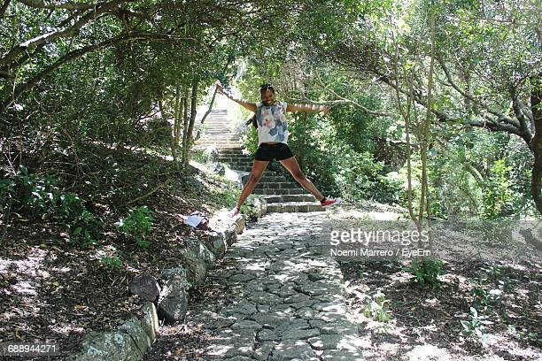 Full Length Portrait Of Happy Woman Jumping Over Footpath In Forest