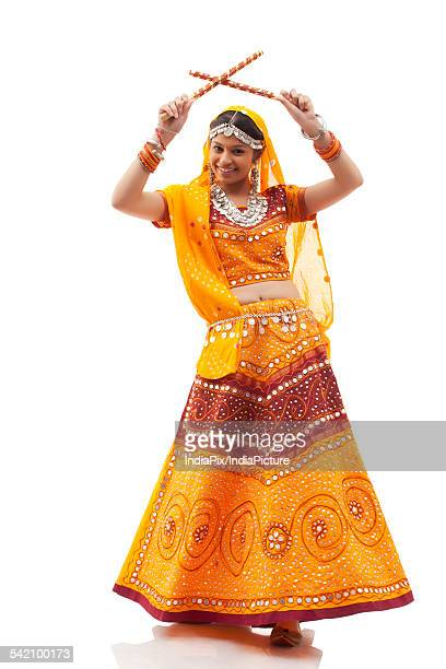 Full length portrait of happy young woman playing Dandiya Raas isolated over white background