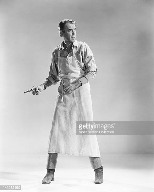 Full length portrait of James Stewart US actor wearing an apron and holding a pistol in a studio portrait issued as publicity for the film 'The Man...