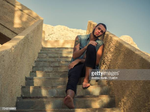 Full Length Portrait Of Man Relaxing On Steps