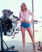 Full length portrait of Michelle Pfeiffer US actress wearing a pink blouse tied at the waist and a pair of denim hot pants posing beside an engine...