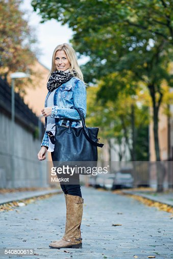 Full length portrait of mid adult woman standing on street