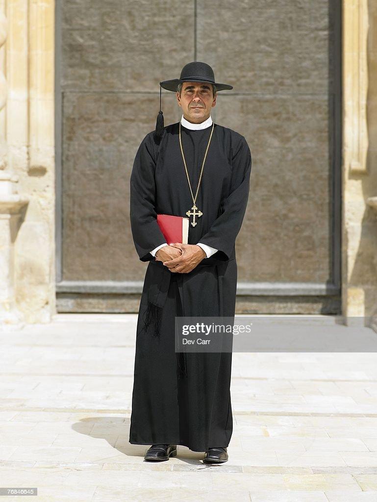 Full length portrait of priest by ornate door, Alicante, Spain,