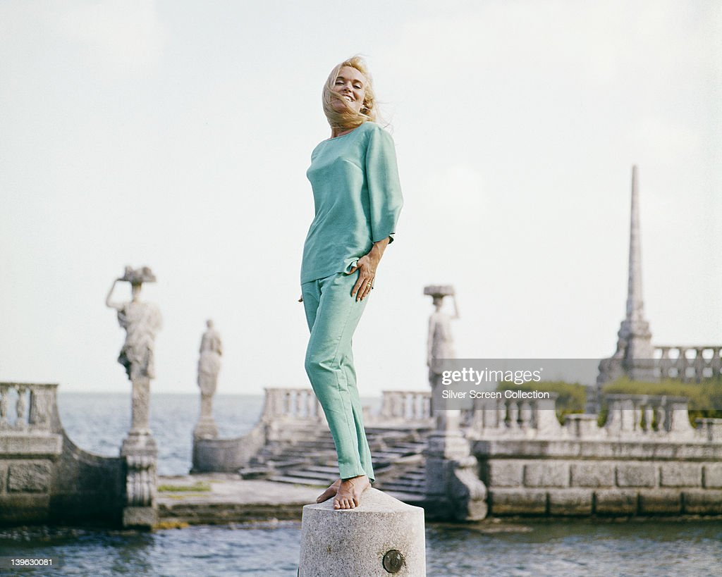 Full length portrait of <a gi-track='captionPersonalityLinkClicked' href=/galleries/search?phrase=Shirley+Eaton&family=editorial&specificpeople=900615 ng-click='$event.stopPropagation()'>Shirley Eaton</a>, British actress, wearing a light blue top with matching trousers while posing with statuary at the water's edge beyond, circa 1965.