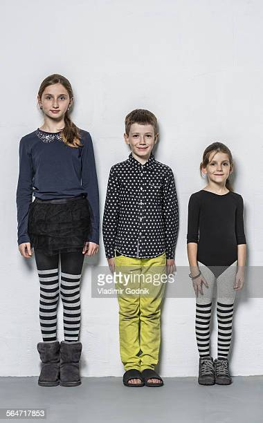 Full length portrait of smiling brother with sisters standing side by side against wall