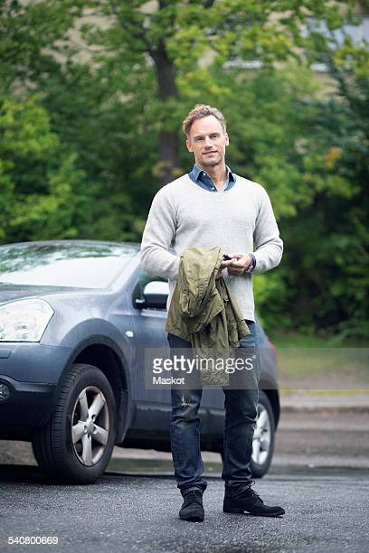 Full length portrait of smiling mature man standing against car