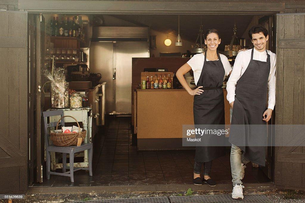 Full length portrait of smiling owners standing outside restaurant