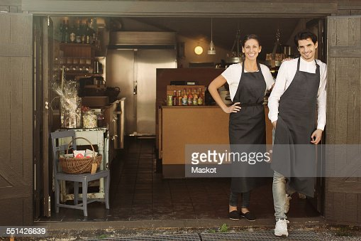 Full length portrait of smiling owners standing outside restaurant