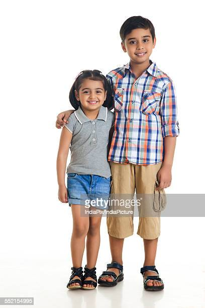 Full length portrait of smiling siblings standing against white background