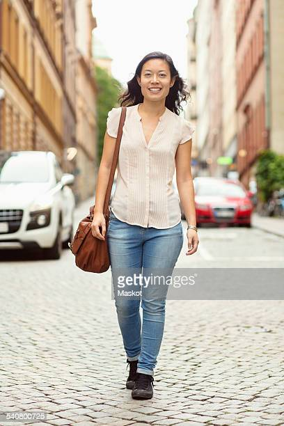 Full length portrait of smiling woman walking on city street