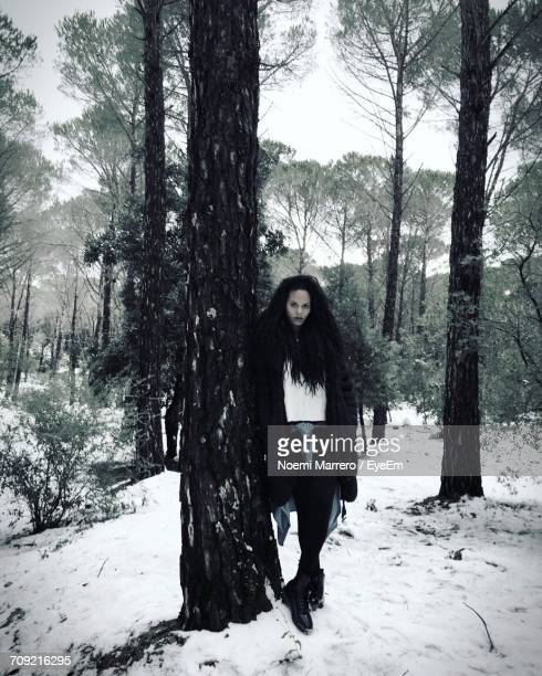 Full Length Portrait Of Woman Leaning On Tree In Snow Covered Forest