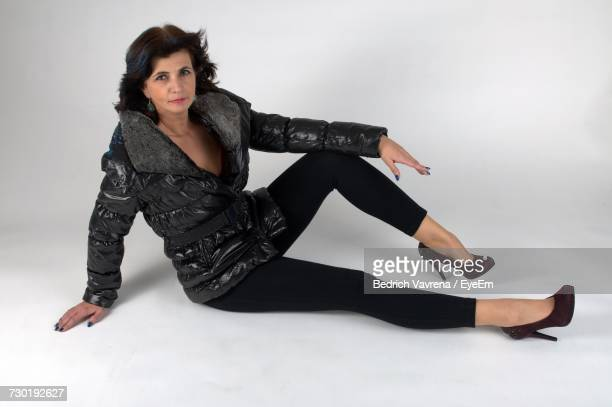 Full Length Portrait Of Woman Wearing Jacket While Sitting Against White Background