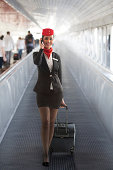 Full length portrait of young air hostess pulling luggage while answering smart phone on airport escalator