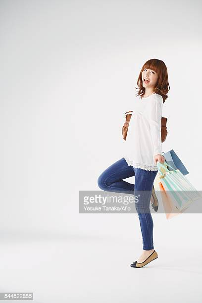 Full length portrait of young Japanese woman against white background