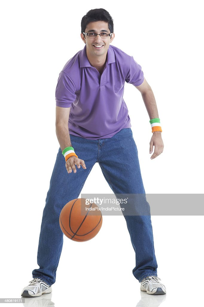Full length portrait of young man playing basketball over white background